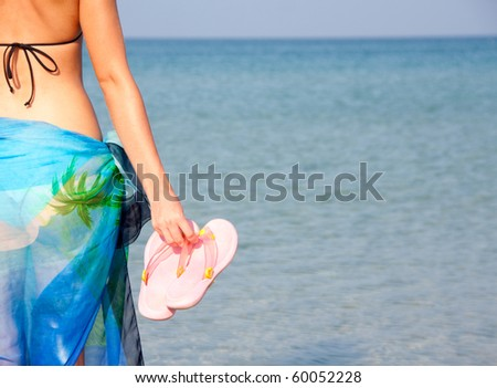 Woman in bikini with pink flip flops by the sea