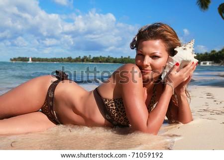 Woman in bikini with seashell on tropical beach
