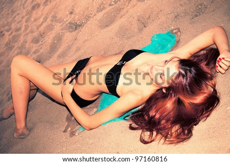woman in black bikini on sand beach, retro style colors, small amount of grain added, full body shot