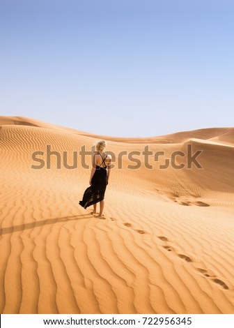Woman in black dress goes in on yellow sand in desert, back view