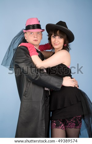 Woman in black hat and dress  and a man in pink hat
