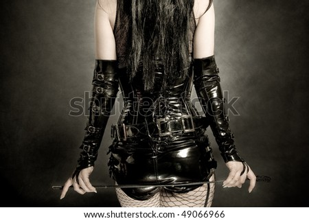 woman in black latex corset, with horsewhip in hands