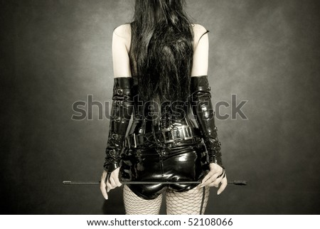 woman in black latex uniform with horsewhip in hands, back