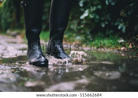 Woman in black rubber boots standing in a puddle while it's raining. Focus on boots. #515662684