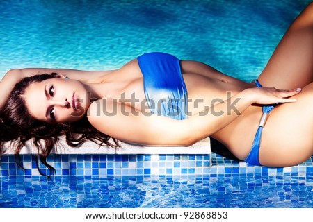 woman in blue bikini lie by the pool, summer day - stock photo