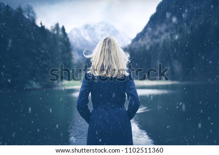 Woman in blue coat standing at lake during snowfall. Selective focus used.