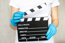 Woman in blue disposable rubber gloves holding movie clapper. Influence of pandemic on cinematography