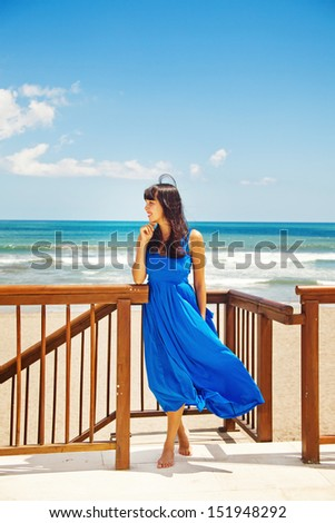 woman in blue dress at luxury beach