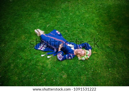 Woman in blue embroidered dress and in wreath of flowers, lies on grass #1091531222