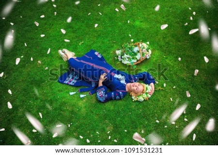 Woman in blue embroidered dress and wreath of flowers lies on grass. Falling flower petals #1091531231