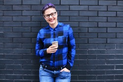 Woman in Blue Flannel Holding Paper Cup Against Black Wall