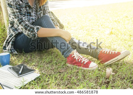 woman in blue jean and red canvas sneakers sitting on green grass,bright and sunny day #486581878