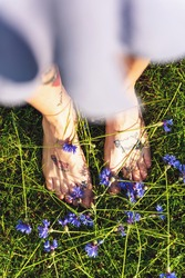 Woman in Blue Summer Dress with Tattooed Bare Feet Standing  on Grass and Cornflower Flowers.
