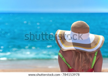Woman in bonnet hat and swimsuit is sitting on the ground and looking at the sea. Back view. #784153978