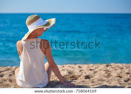 Woman in bonnet hat relaxing on the beach. #758064169