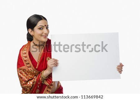 Woman in bright red mekhla holding a placard