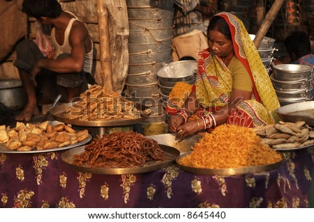 Woman in brightly colored sari selling indian sweets from a market stall.