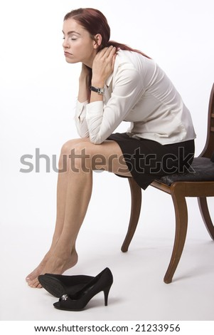 Woman in business attire sitting with her shoes off, looking exhausted