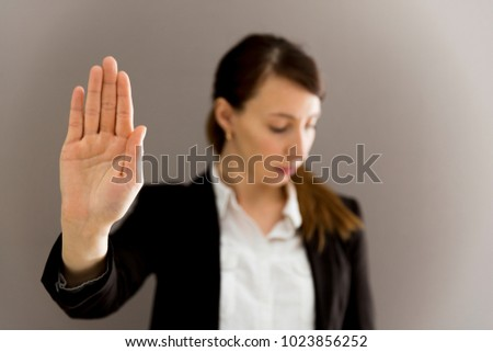 Woman in business suit showing her palm, body language, say NO at work, self-awareness #1023856252