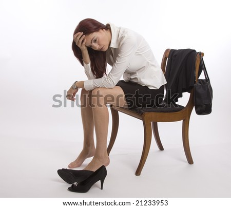 Woman in business suit sitting on a chair looking exhausted - stock photo