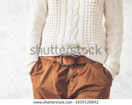 Woman in cable-knit white sweater with Scandinavian pattern and brown chinos trousers with leather belt. Casual clothes for snuggle weather. Modern urban fashion. Foto stock ©