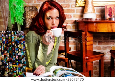woman in cafe drinking coffee and reading magazine