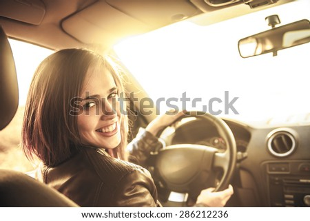 woman in car indoor keeps wheel turning around smiling looking at passengers in back seat idea taxi driver talking to police companion companion who asks for directions right to drive Documents exam