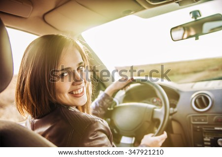 woman in car indoor keeps wheel turning around smiling looking at passengers in back seat idea taxi driver against sunset rays Light shine sky Concept of exam Vehicle - second home the girl