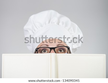 Woman in chief's hat looking over the cookbook  on grey background