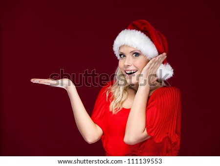 Woman in Christmas cap gestures palm up, isolated on purple