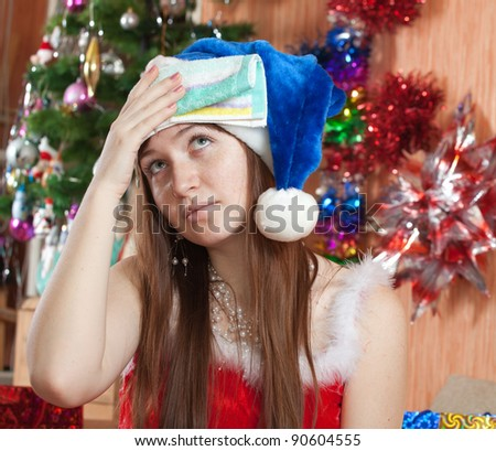 Woman in christmas hat having hangover at home