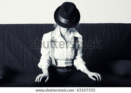 Woman in classic men\'s hat, and a shirt sitting on the sofa