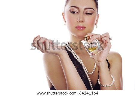 Woman in classic style applying perfume on her wrest. Focus on hands and bottle. - stock photo