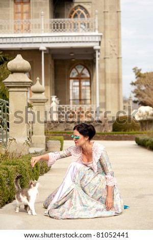 woman in classical dress goes through the alley next to the cat
