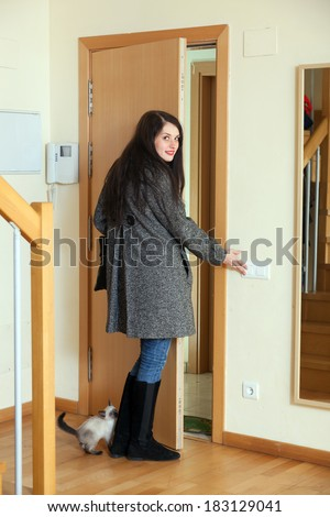 Woman in coat turns off the light and leaving  home