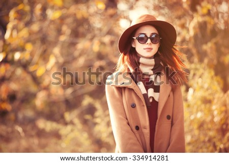 Stock Photo Woman in coat with hat and scarf in autumn park