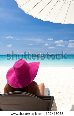 Woman in color hat sitting in chaise longue
