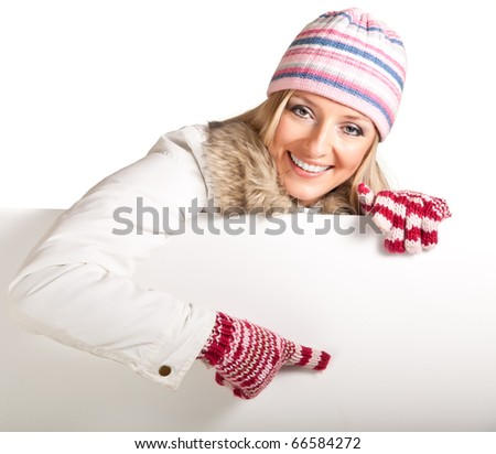 Woman in colorful hat and gloves peeping from behind whiteboard isolated on white