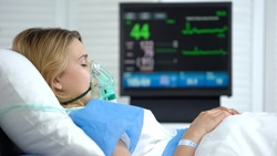Woman in coma, heart rate falling on ecg monitor, intensive care hospital unit