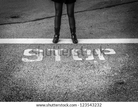 "Woman in combat boots standing strong with word ""Stop"" under her feet. #123543232"