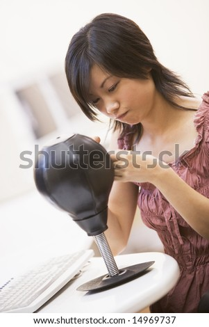 Woman in computer room sitting by small punching bag