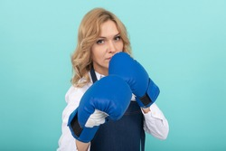 woman in cook apron punching boxing gloves, knockout.