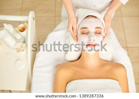 Woman in cosmetic mask lying down in the beauty salon.