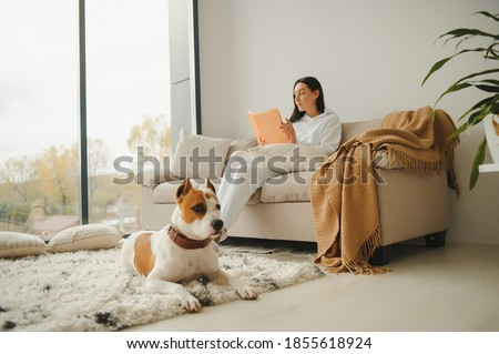 Woman in cozy home clothes relaxing at home with dog reading a book. Comfy lifestyle.