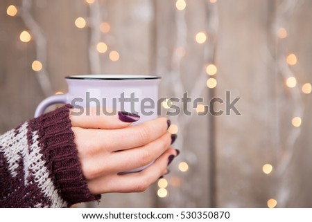 Woman in cozy sweater holding a cup of tea #530350870