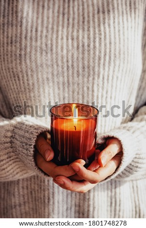 Woman in cozy sweater holding burning candle close-up. Cozy autumn or winter, hygge lifestyle