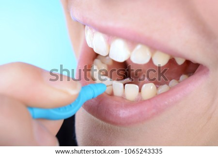 Woman in dental care of interdental spaces with dental brush