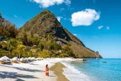 woman in dress and summer hat walking at the white tropical beach, Sugar beach St Lucia or Saint Lucia Caribbean