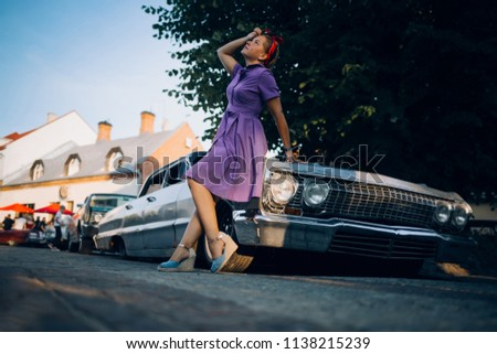 Woman in dress in front of old muscle car