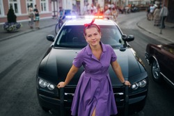 Woman in dress near police car